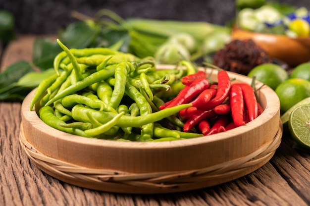 Fresh chili on a wooden tray with lemon and kaffir lime leaves.
