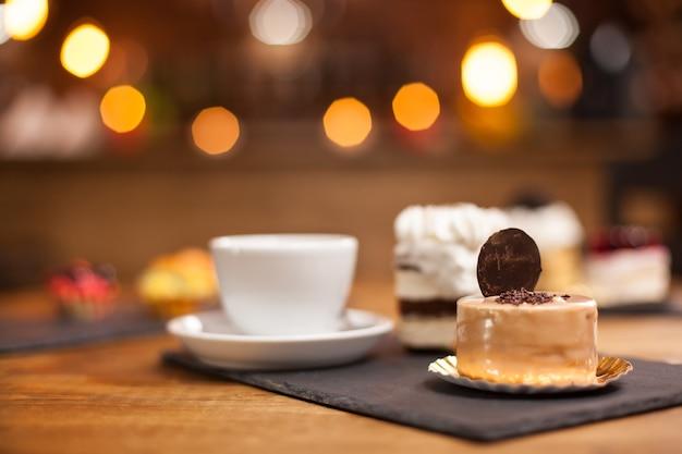 コーヒーショップで甘いビスケットをのせた新鮮なチョコレートケーキ。コーヒーショップの木製テーブルの上に甘いミニケーキ。おいしいデザート。コーヒーショップの名物。