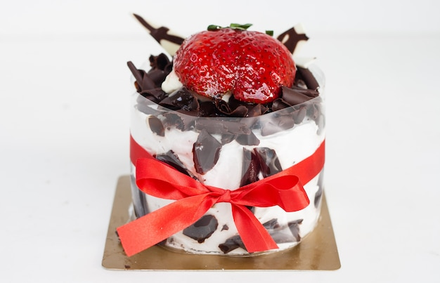 Fresh chocolate cake with strawberries on white surface