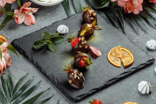 Свежая клубника в шоколаде на сером декоративном фоне. концепция рекламы летнего сезонного меню.