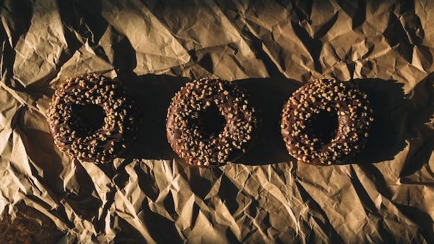 しわくちゃのクラフト紙に新鮮なチョコレートドーナツ