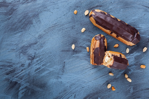 Fresh chocolate eclairs and peanuts placed on blue background.