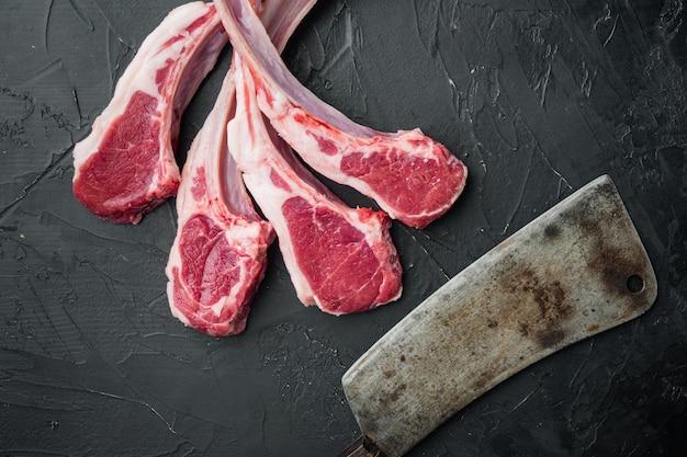 신선한 다진 송아지 고기 랙 요리 세트 및 오래된 정육점 칼, 검은 돌 테이블, 평면도 평면 누워
