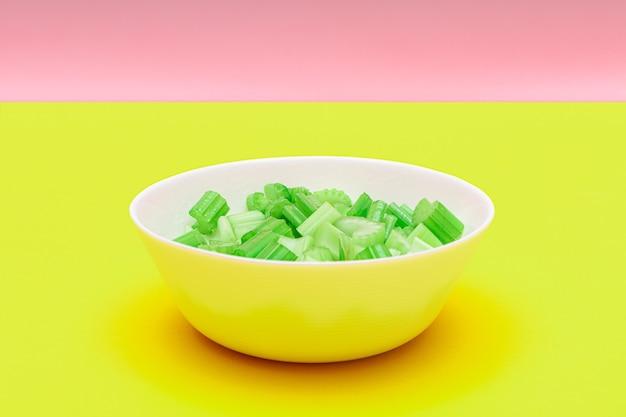 흰색 그릇에 물방울이 있는 신선한 다진 셀러리 피스