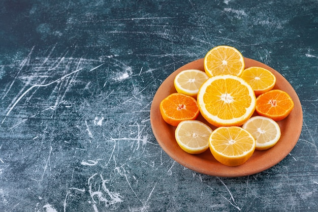 Fresh chopped citrus fruits placed in a clay round plate .