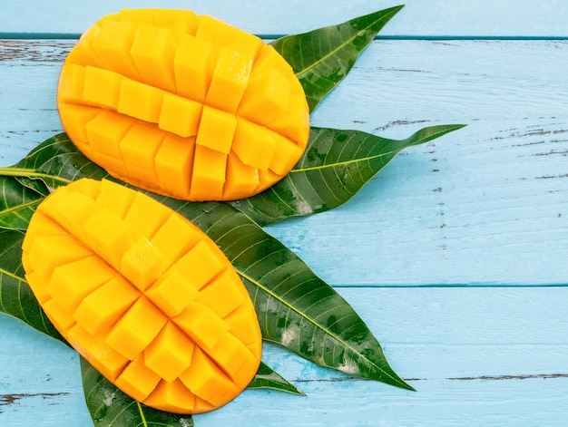 Fresh chopped mango with green leaves on bright blue color timber background