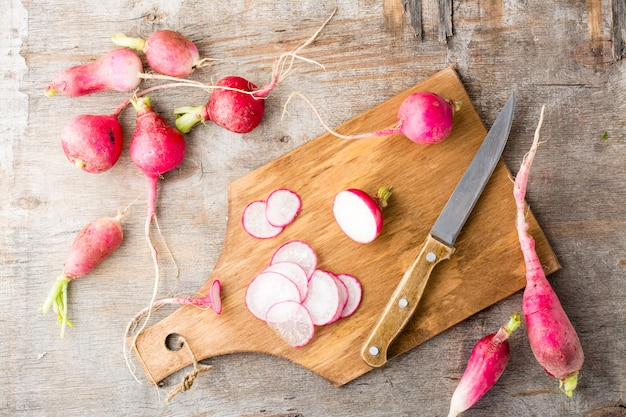 Fresh chopped radishes and a knife on a cutting board on a wooden table. rustic style. top view