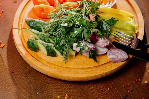 木の板にみじん切り野菜。フレッシュトマト、キュウリ、大根、ハーブの前菜。トップビュー。健康的な食事、食事、菜食主義の概念。