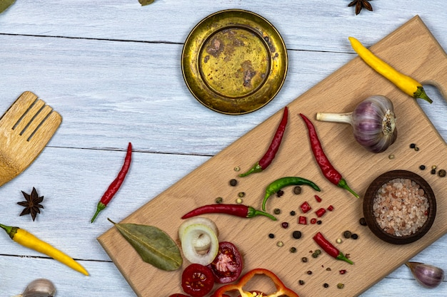 新鮮なみじん切り野菜、スパイス、調味料の台所用品、白い木製の背景にまな板。