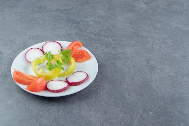 Fresh chopped vegetables on white plate.