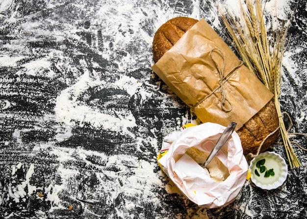 小麦粉の袋と小麦の穂が付いた新鮮なチャバタ。小麦粉と一緒にボード上。テキスト用の空き容量。上面図