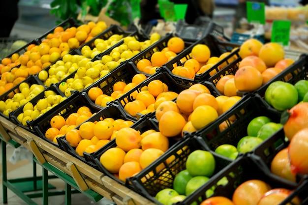 Свежие цитрусовые находятся на полке в магазине. различные цитрусовые. апельсины, мандарины, лайм, лимоны. супермаркет