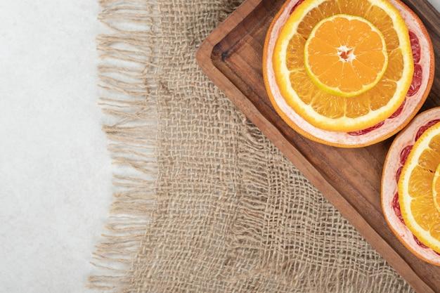 Fresh citrus fruit slices on wooden board