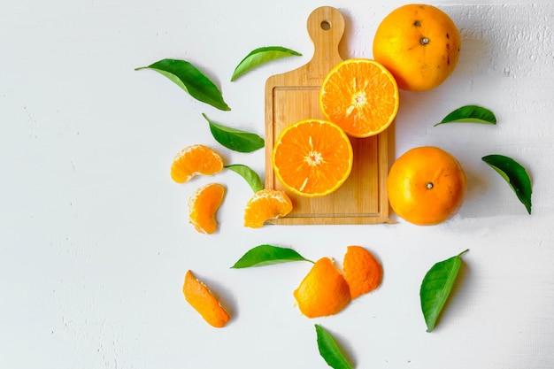 カットしたオレンジとオレンジの葉が入った新鮮な柑橘系の果物。