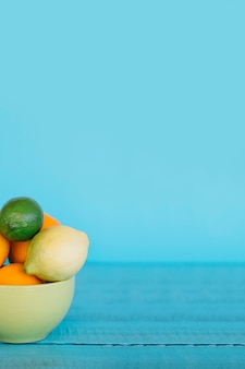 Fresh citrus fruits in bowl on blue wooden table