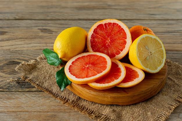 Свежие цитрусовые, лимон, апельсин и известь с листьями на разделочной доске, крупным планом. органические цитрусовые.