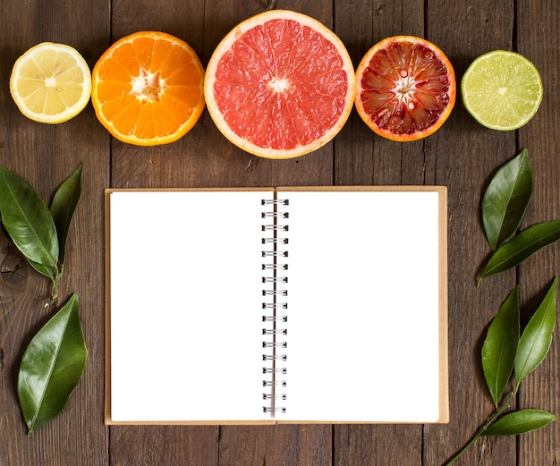 Fresh citrus fruits and notebook on a wooden table