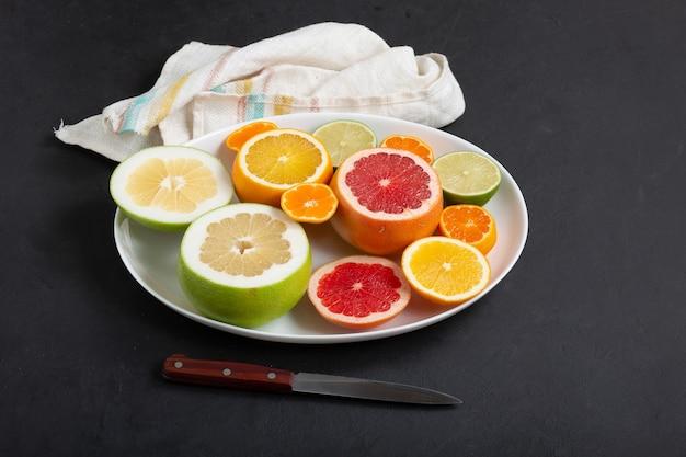 白い皿の上の新鮮な柑橘系の果物がクローズアップ、暗い背景