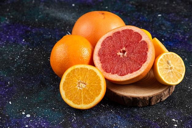 목 판에 신선한 감귤 류의 과일입니다. 전체 또는 절반 절단.