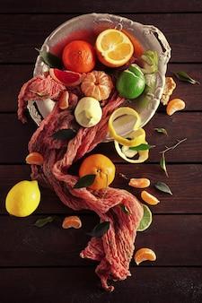 木製のテーブル、上面図に緑の葉と新鮮な柑橘系の果物