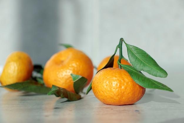 葉のある新鮮な柑橘系の果物:木箱にレモン、オレンジ、みかん