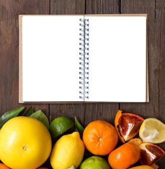 コピースペース付きの木製テーブルの上のノートと新鮮な柑橘系の果物