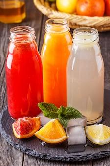 Свежие цитрусовые соки в стеклянных бутылках