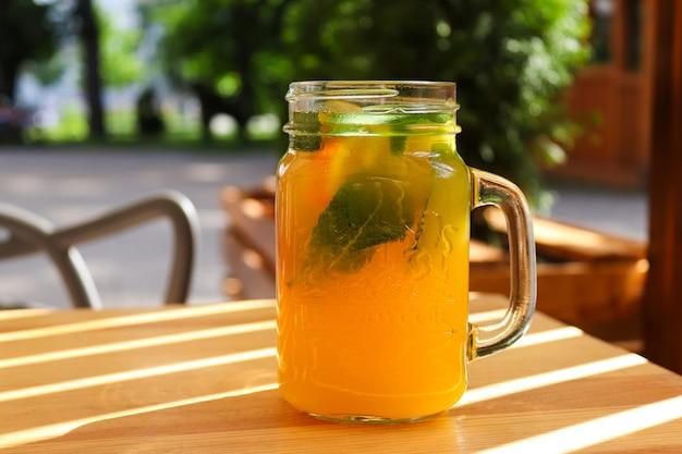 오렌지 민트와 얼음이 든 항아리에 신선한 감귤류 레모네이드가 나무 탁자에 있는 여름 다과