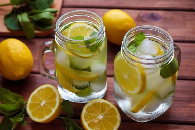木製のテーブルの上の瓶にレモン、ミント、氷と新鮮な柑橘類のレモネード