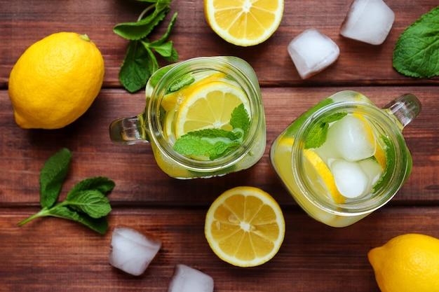 木製のテーブルにレモンミントと氷と新鮮な柑橘類のレモネード夏のさわやかな飲み物