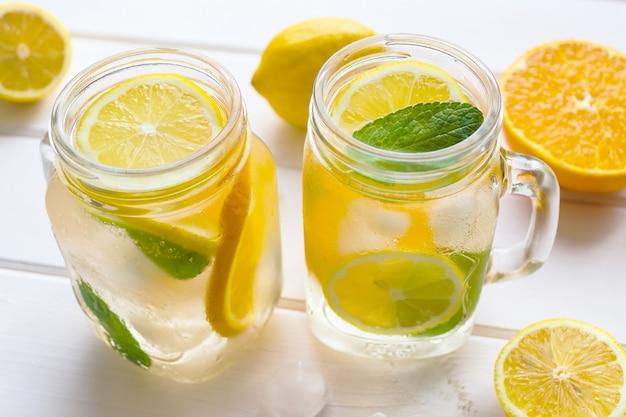 白い木製のテーブルにレモンオレンジミントと氷と新鮮な柑橘類のレモネード夏のさわやかな飲み物