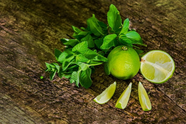 Fresh citrus lime with mint close up on wooden table. mojito