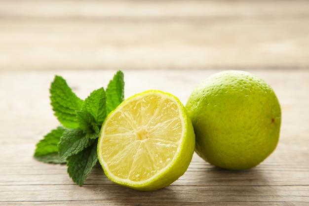 Fresh citrus lime with mint on grey wooden wall