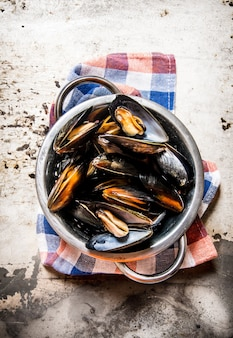 Fresh clams in a pan with a knife. on rustic background. top view