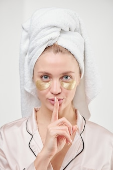 Fresh and clean young woman with towel on head and golden under-eye patches keeping forefinger by her mouth
