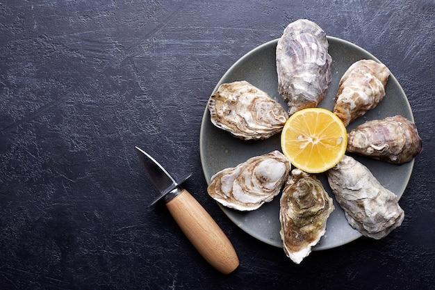 丸いプレートに新鮮な閉じた牡蠣、氷とレモン、石のテクスチャー。