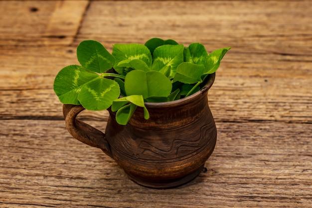세라믹 컵에 신선한 클로버 꽃다발입니다. 행운의 상징, 패트릭의 날 개념