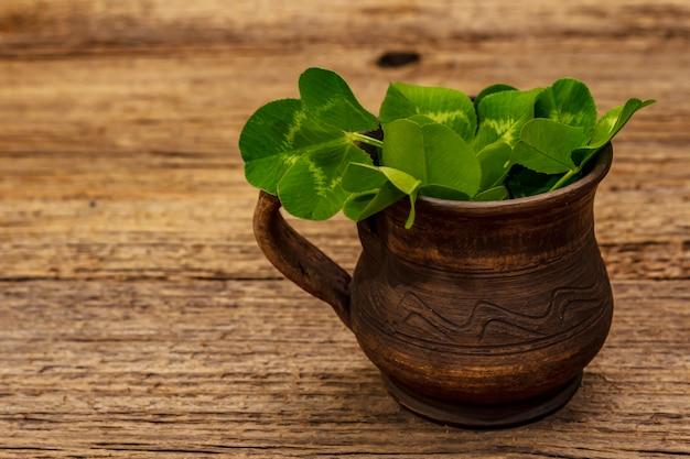 セラミックカップで新鮮なクローバーの花束。幸運のシンボル、聖パトリックの日のコンセプト