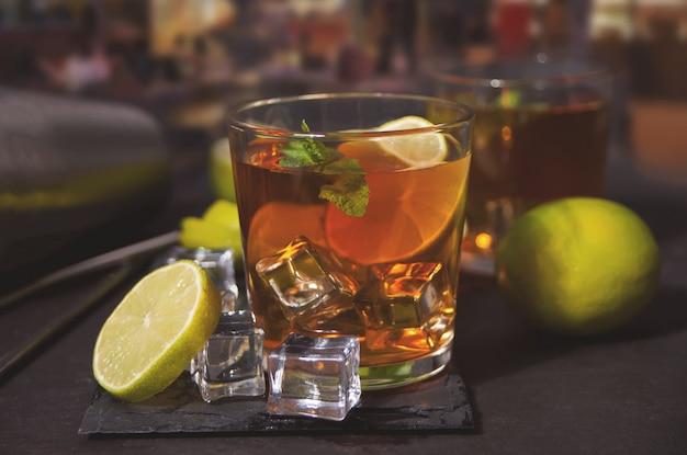 黒い表面に茶色のラム酒、コーラ、ミント、ライムを加えたフレッシュカクテルキューバリブレ。ロングアイランドのアイスティーカクテル。