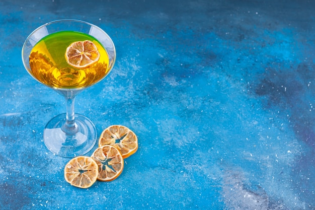 Fresh cocktail and dried lemons placed on blue background.