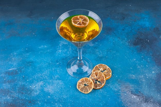 Fresh cocktail and dried lemons placed on blue