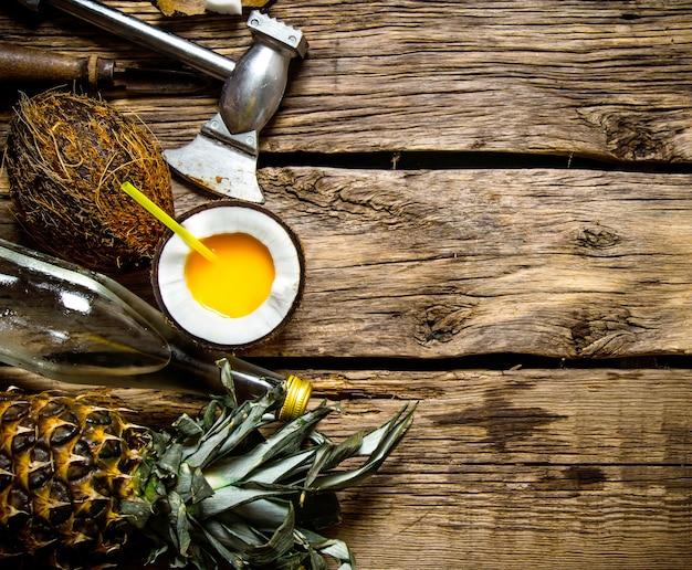 木製のテーブルにココナッツラム酒とパイナップルのカップで新鮮なカクテル。テキスト用の空き容量。上面図