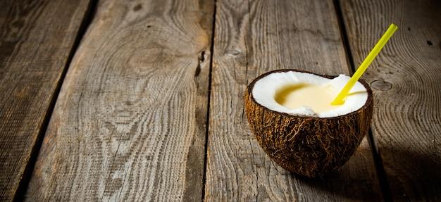 Свежий коктейль в кокосовой чашке на деревянном столе. свободное место для текста.
