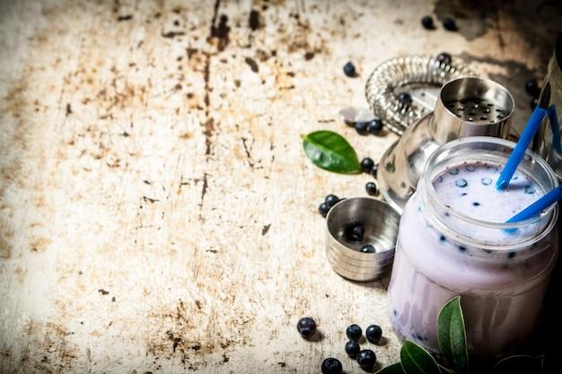 ブルーベリーミルクのフレッシュカクテル。古い素朴な背景に。