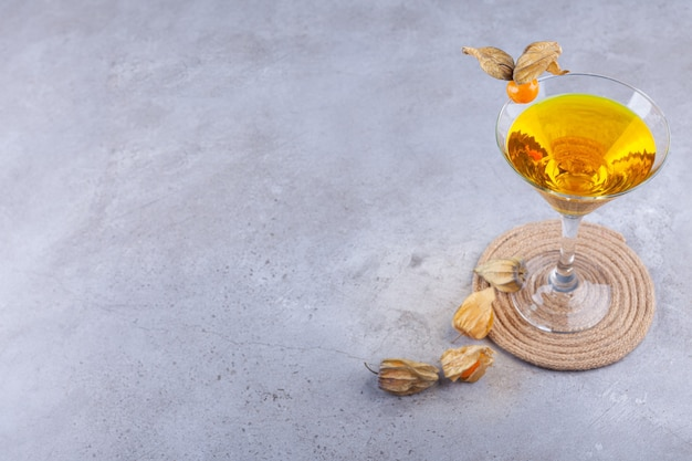 Fresh cocktail and ripe kumquats placed on stone background.