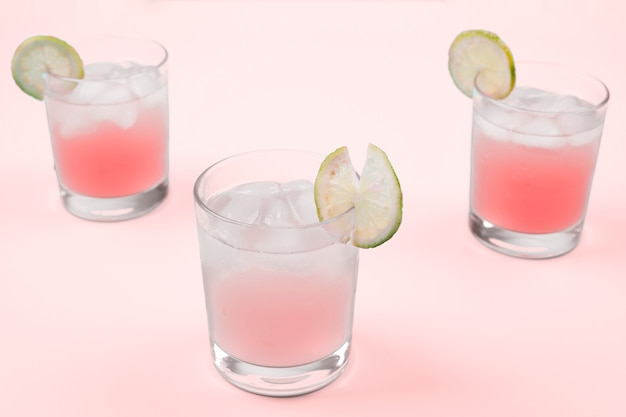 Fresh cocktail with ice cubes and lemon slices against pink background