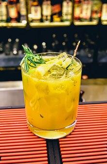 Свежий коктейль с апельсином, лаймом и мятой у барной стойки в ночном клубе