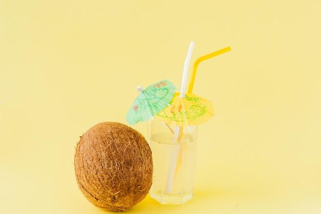 黄色の背景、コピースペースにストローと新鮮なココナッツカクテル。