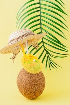 黄色の壁にストローで新鮮なココナッツカクテル。