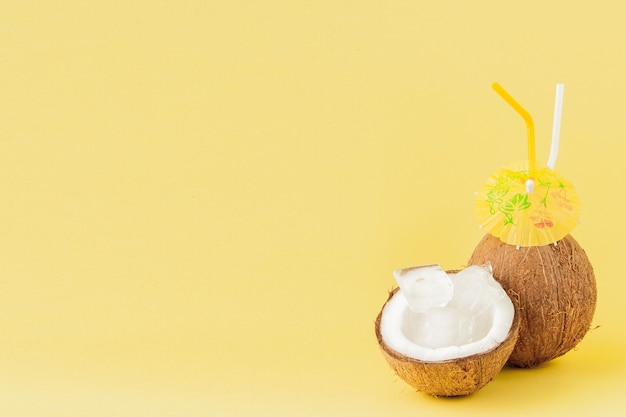 Fresh coconut cocktail with a straws on yellow background, copy space